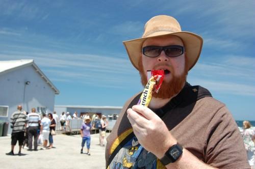 Joel eats a Lunchbar on Robben Island